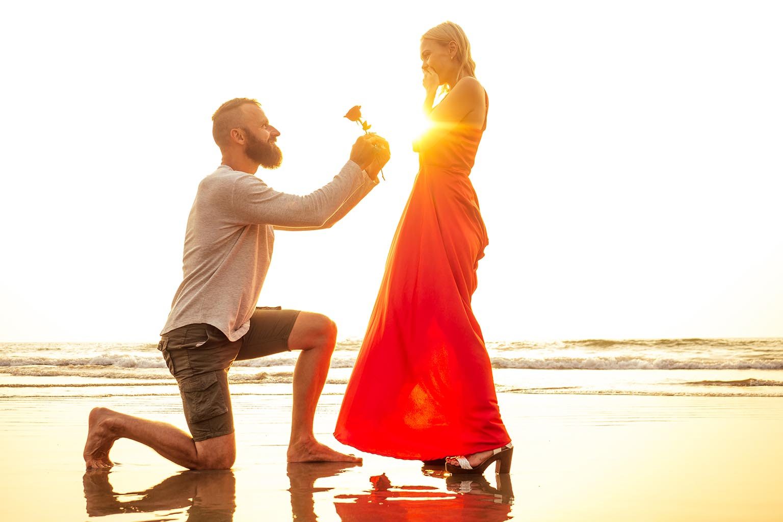 propuesta en la playa de un hombre arrodillado junto a una mujer, con un vestido largo rojo al atardecer