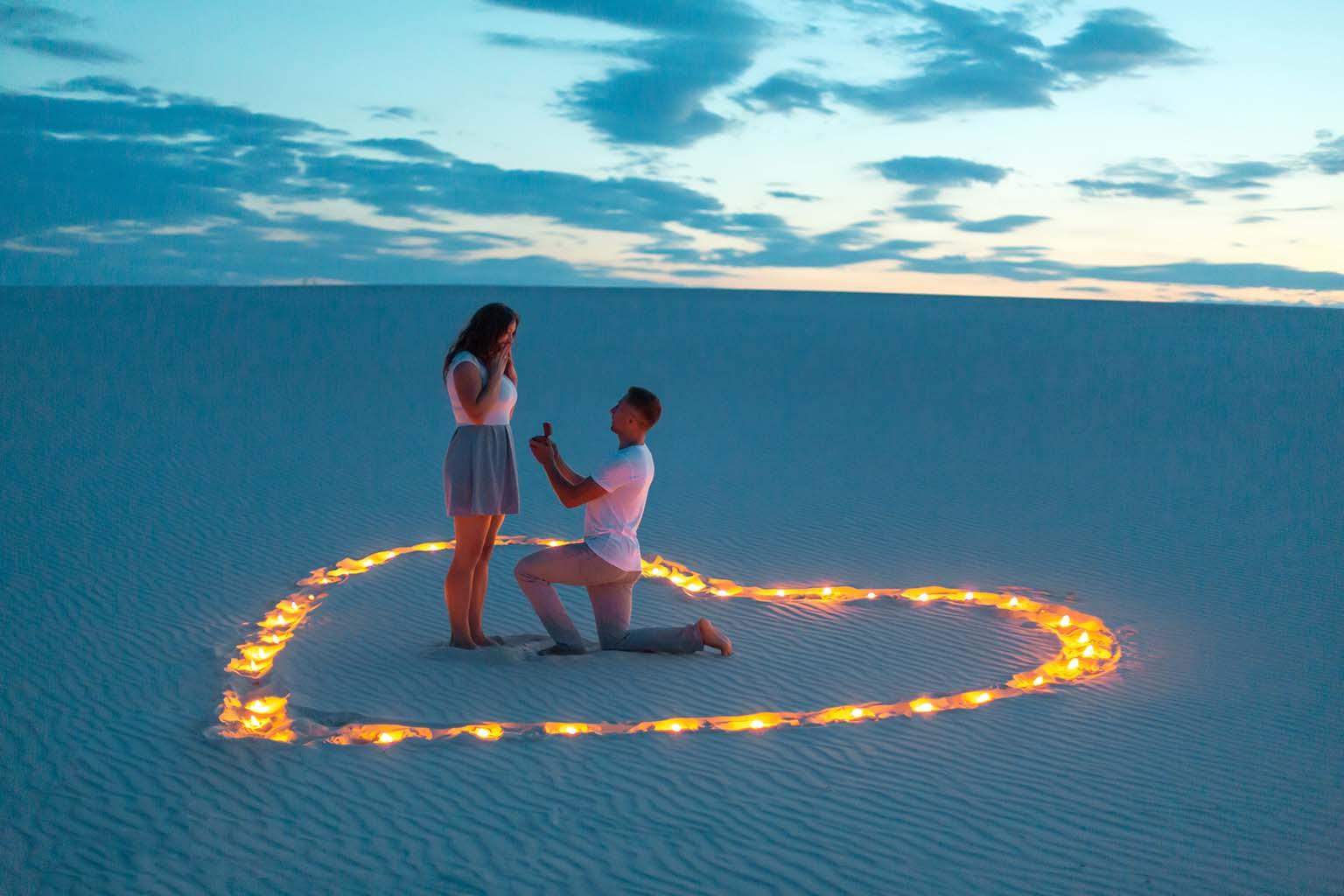 Hombre realiza una propuesta de amor espectacular, arrodillado en la arena dentro de un corazón de fuego