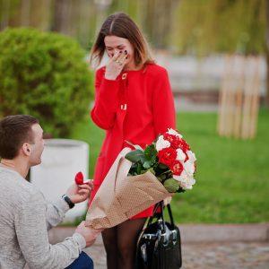 Mujer sorprendida en el parque por su pareja con un anillo y un ramo de rosas, protagonizando una de las sorpresas de amor más originales
