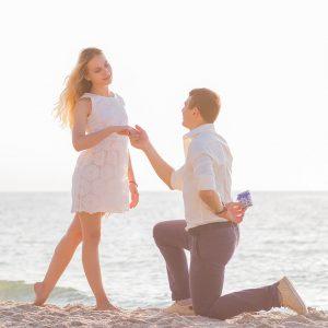 hombre se arrodilla en la arena y realiza una de las mejores pedidas de mano , junto a la orilla del mar, en la playa