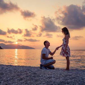 Hombre se arrodilla en la arena de la playa dando lugar a una de las peticiones de mano más espectaculares, justo al atardecer cuando cae el sol