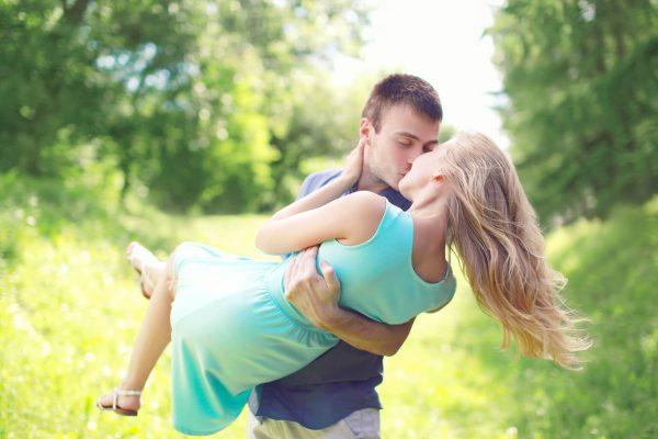 hombre y mujer enamorados se besan con la mayor de las sorpresas, al encontrarse por sorpresa cerca de un parque para parejas