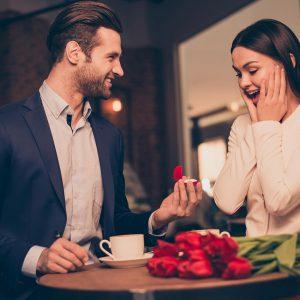 Hombre en una cafetería rústica,sorprende a su pareja con una de las pedidas de mano más románticas