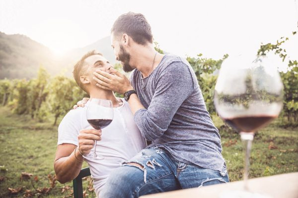 Pareja del colectivo lgtbi se encuentran tomando una copa de vino en unos viñedos, sentados uno encima del otro mirándose fijamente a los ojos