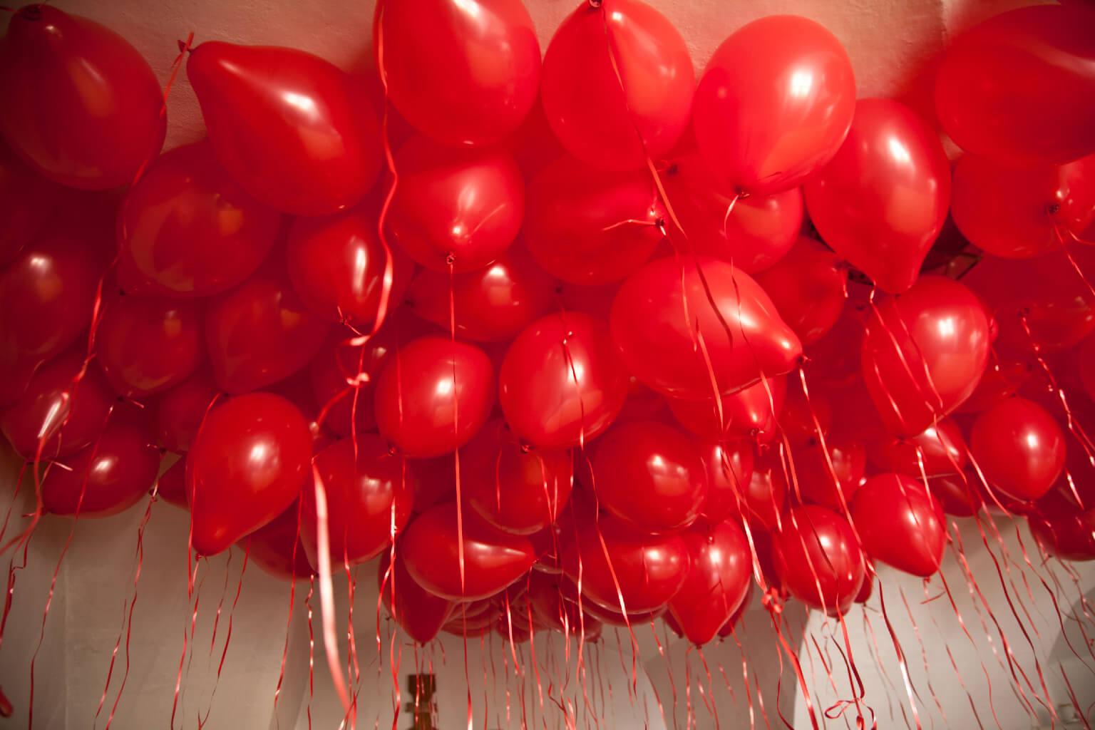 muchos globos de corazón rojo llenos de helio en el techo.