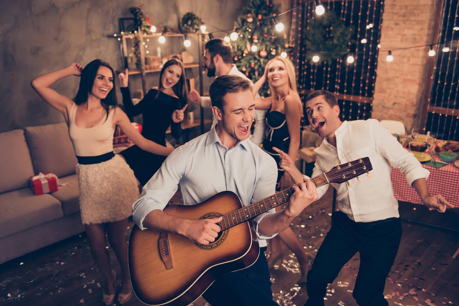 Celebrando el año nuevo. ¡El joven músico guapo hace ruido con su instrumento! Grupo de jóvenes festivos hermosos en un festín de lujo, muchos brillos en el piso, atuendos elegantes,en un ambiente relajante durante toda la noche.