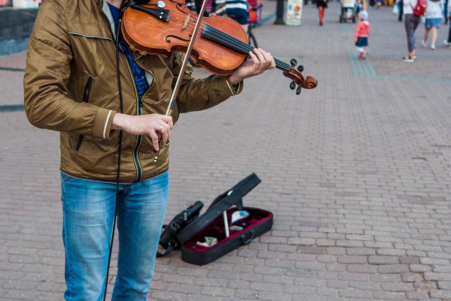 Violinista callejero toca el violín al mediodía, día de otoño.(masculino).