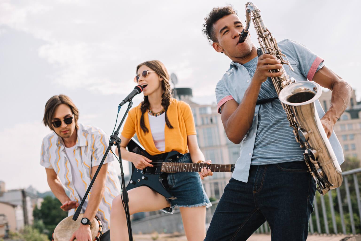 Jóvenes multirraciales con guitarra, djembe y saxofón actuando en la calle