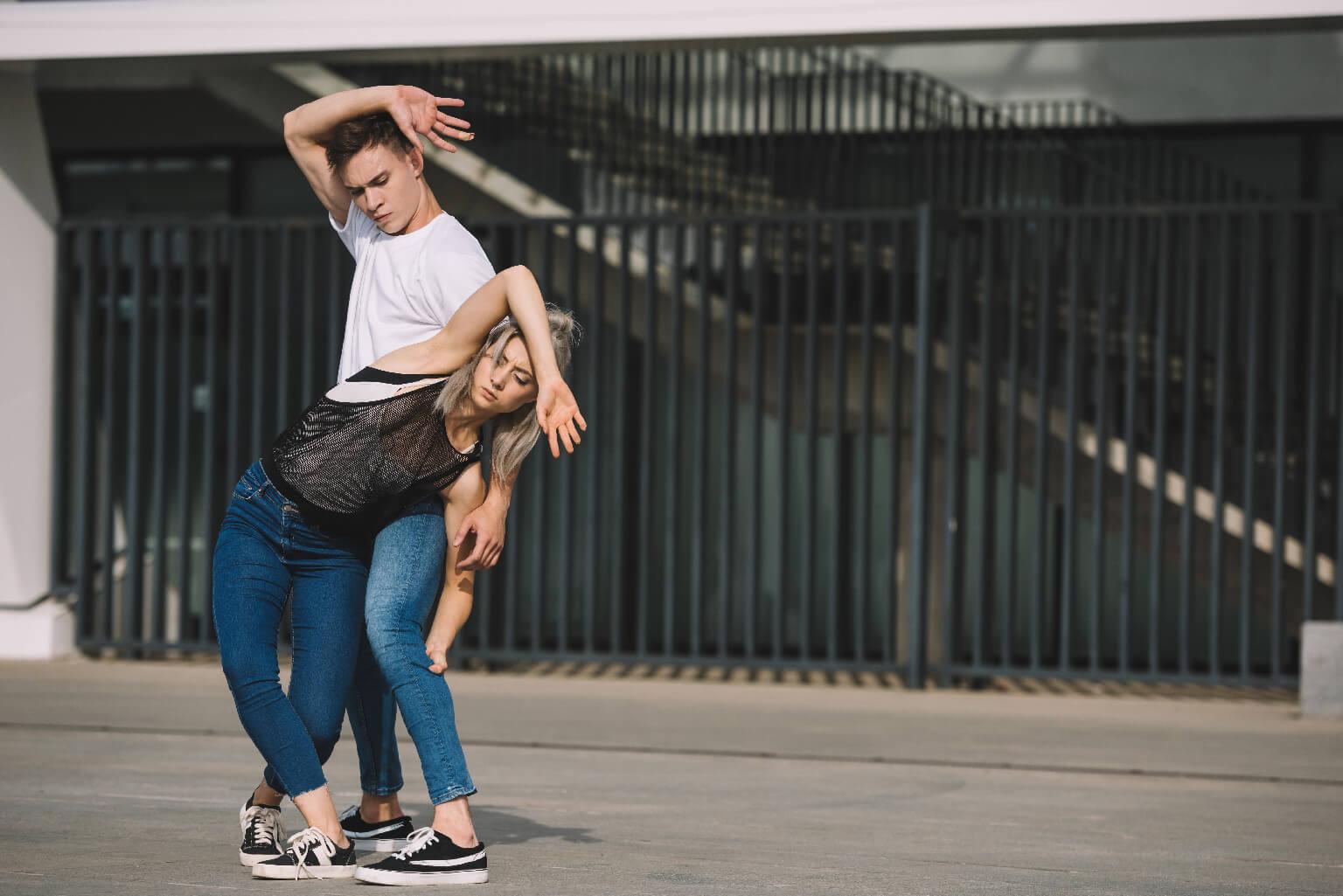 Joven pareja de bailarines practicando en la calle urbana de la ciudad.
