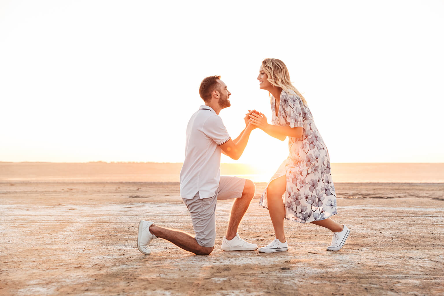 Foto de hombre feliz haciendo una propuesta a su mujer encantada con el anillo mientras caminaba por la playa soleada.
