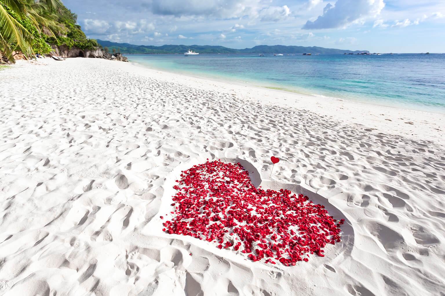 Corazón hecho en la playa junto al mar ,relleno de pétalos de rosa.