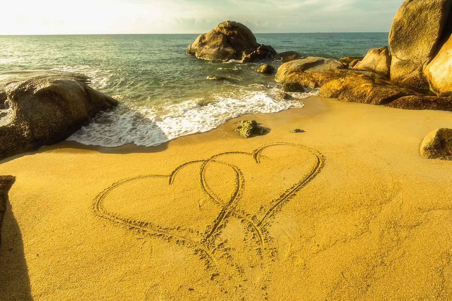 corazones dibujados en la arena, junto a la costa del mar, esperando sorprender a una chica con una de las formas más originales de pedir matrimonio