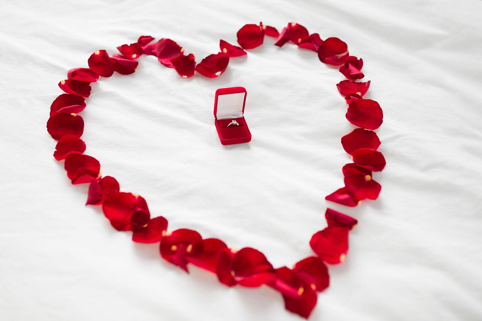 corazón hecho de pétalos y anillo de diamantes en una caja de regalo.