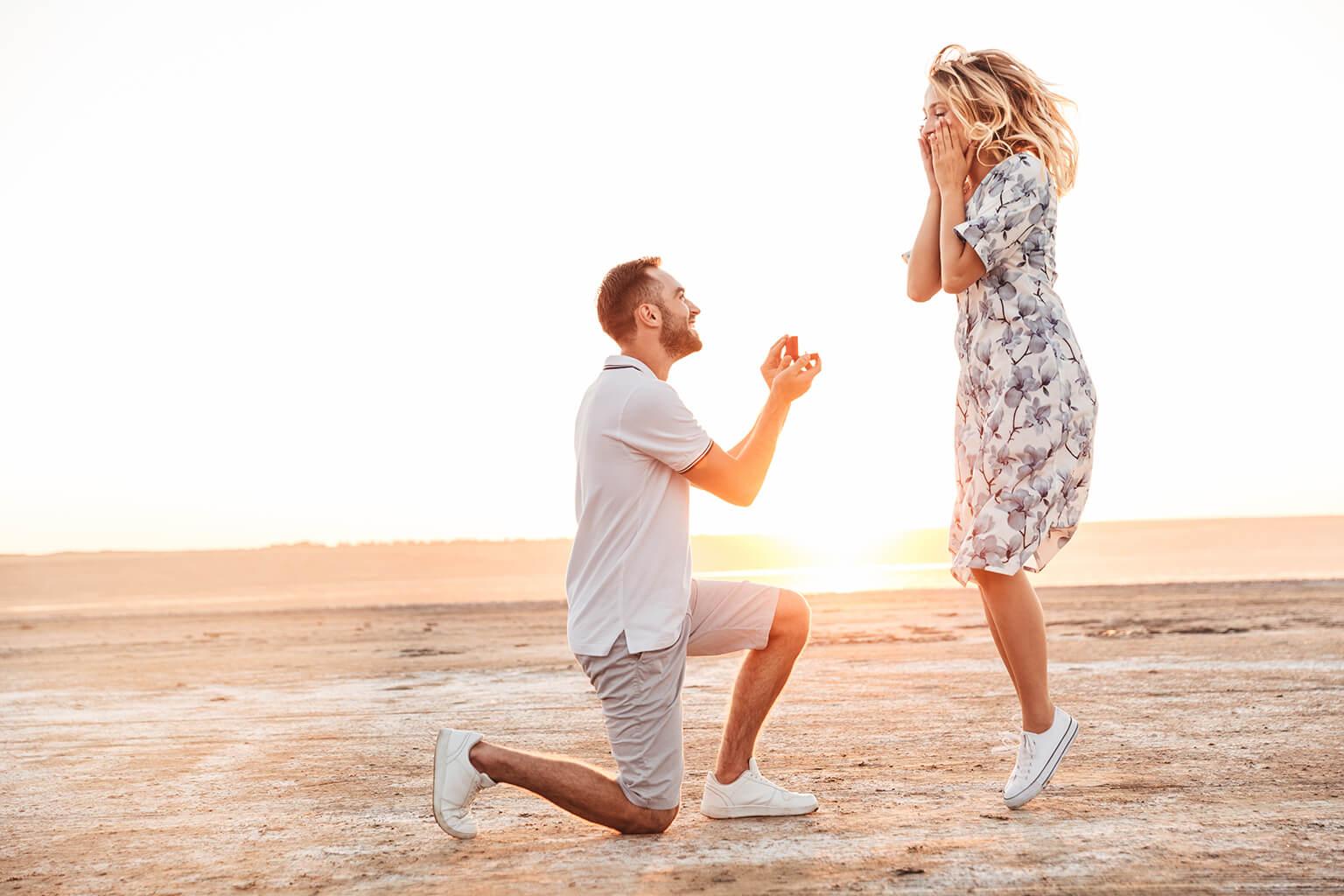 Mujer salta de la alegría en la playa, al ver a su pareja arrodillarse con un anillo de compromiso