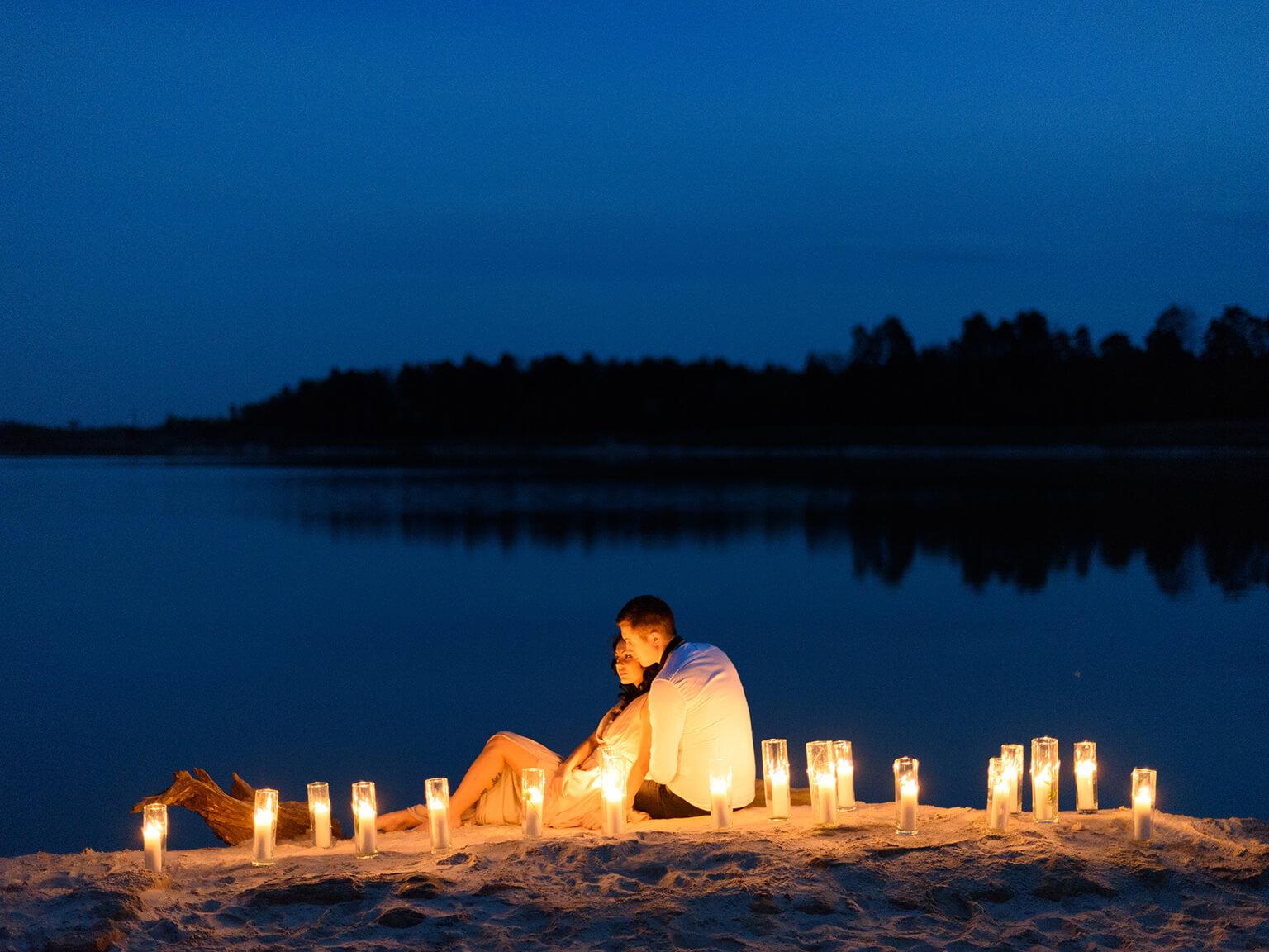 Hermosa joven pareja de enamorados en el lago rodeado de muchas velas encendidas. Tiempo en una noche romántica