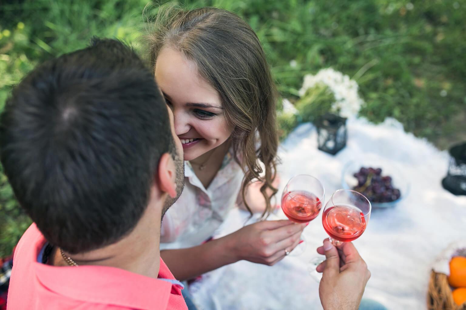 Pareja en un picnic,sonrientes y brindando con vino rosado.