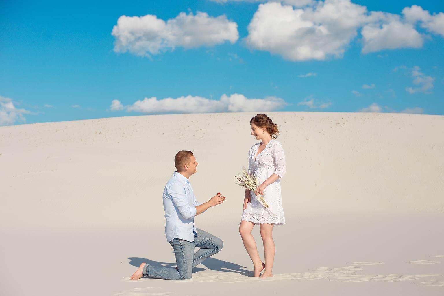 hombre se arrodilla en la arena y sorprende a su pareja, ofreciéndole un anillo de compromiso