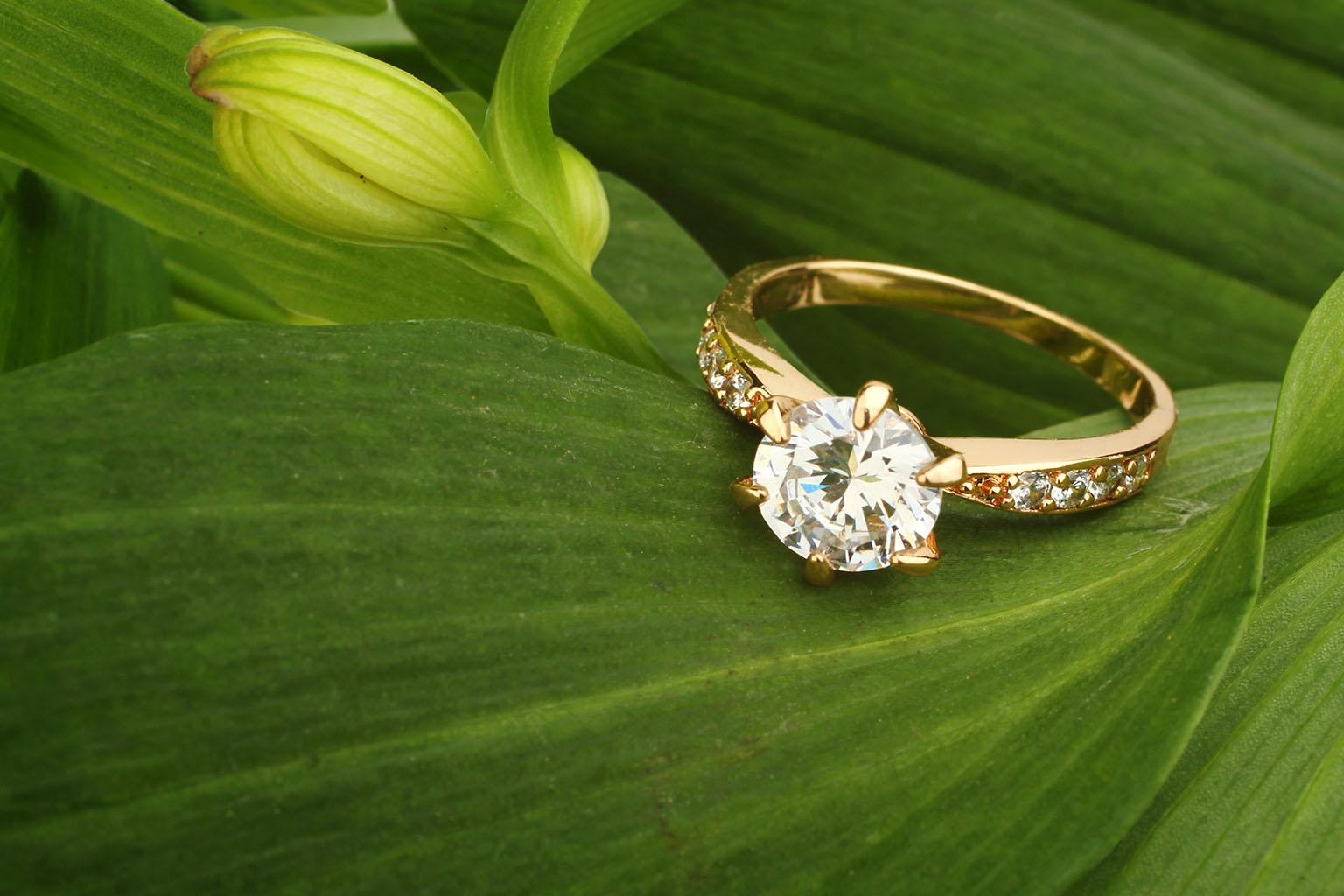 Anillo de oro presentado en una hoja verde con un diamante grande en su base e incrustaciones de diamantes pequeños a su alrededor, uno de los anillos de compromiso más codiciados.