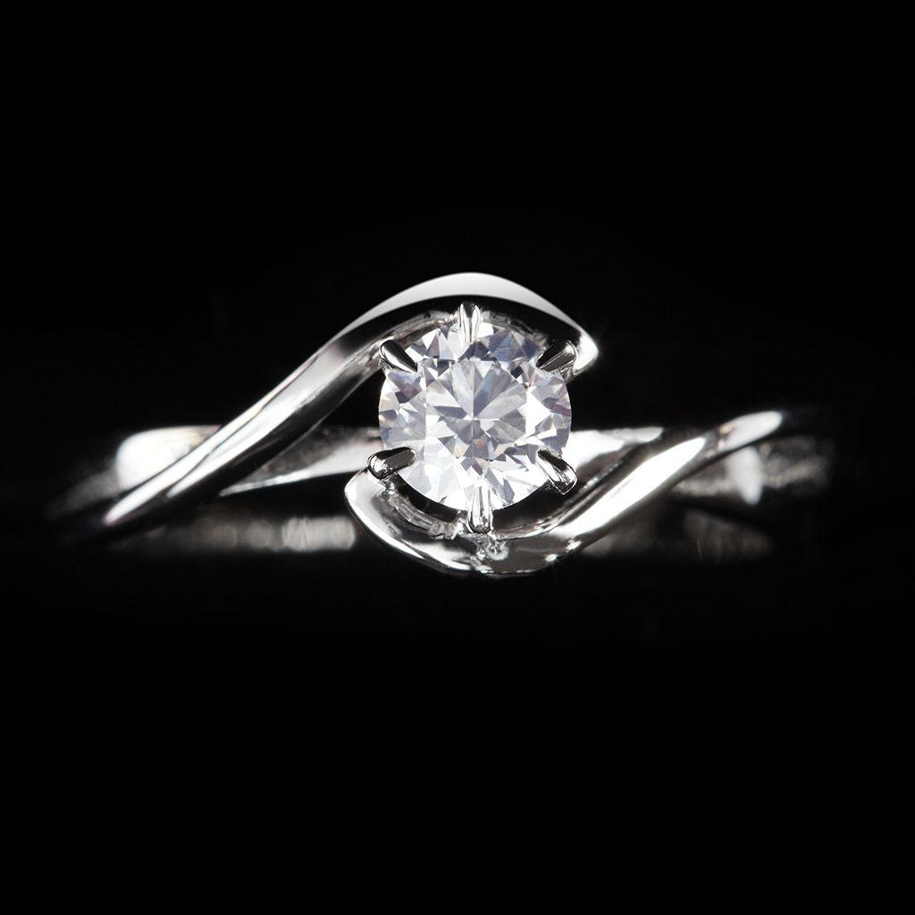 Espectacular anillo de plata con un gran diamante en un fondo negro. Uno de los anillos de compromiso más bonitos a unos precios sin igual.