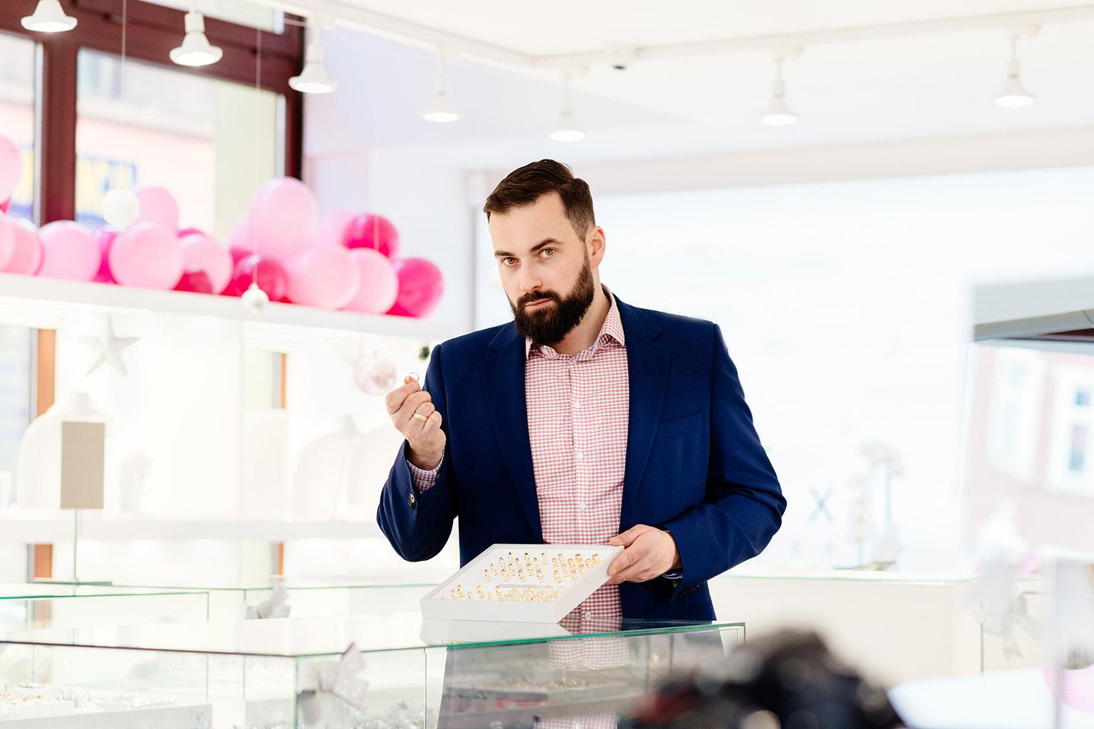 Hombre sosteniendo un anillo, mientras mira muchos anillos de compromiso en una joyería