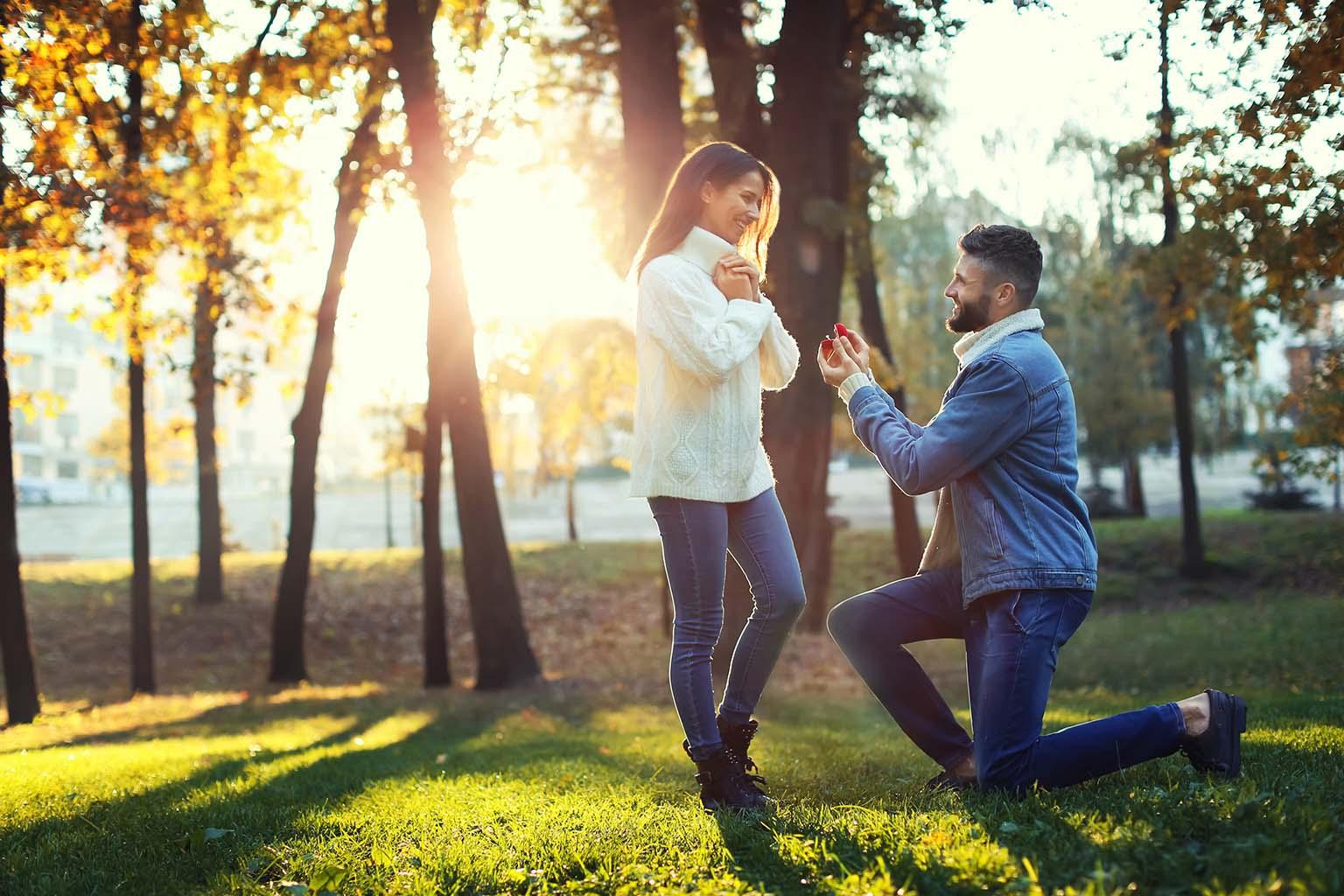Hombre se arrodilla y le ofrece a su pareja un anillo de compromiso en el parque, una de las pedidas más simples, pero de las más bonitas.