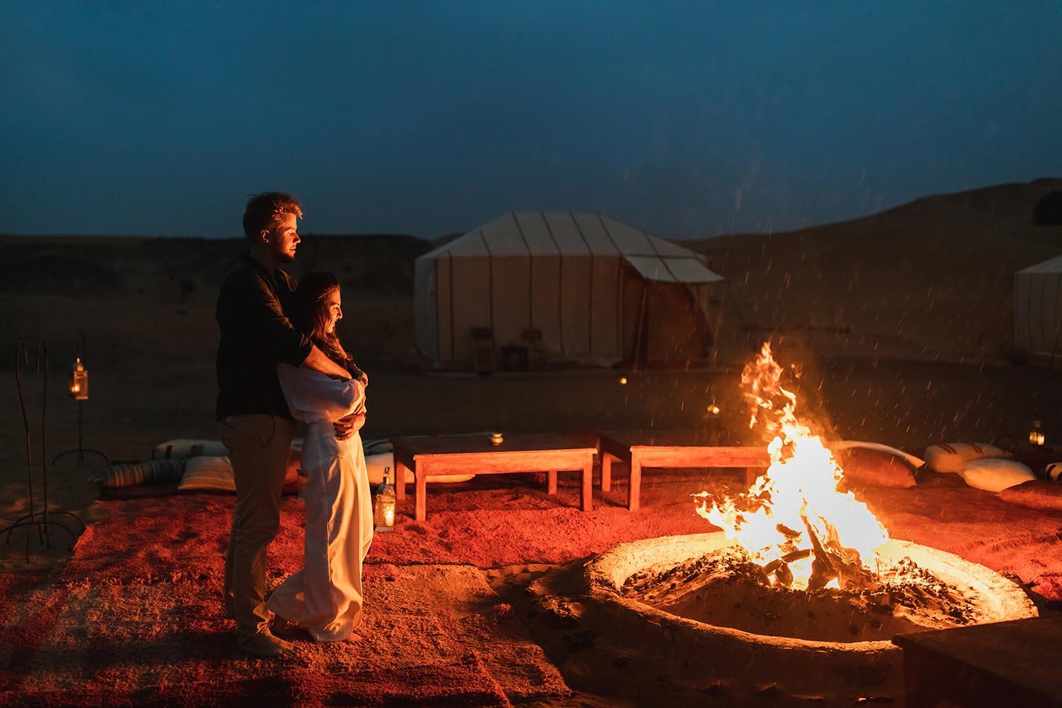 pareja abrazada junto a la luz de una fogata, recuerdan juntos una de las pedidas de matrimonio más ardientes