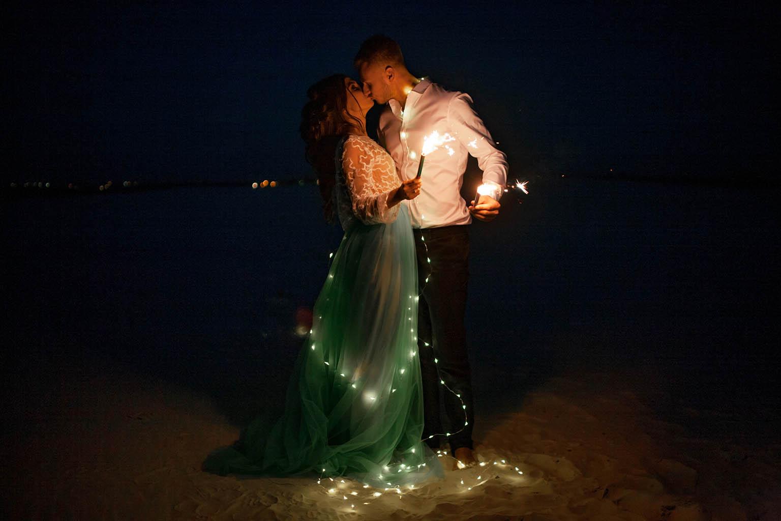 Pareja se besa en la arena, rodeados de luces pequeñas por todo su cuerpo, mientras sostienen unas bengalas, durante una de las pedidas de mano más alucinantes y bonitas del momento.
