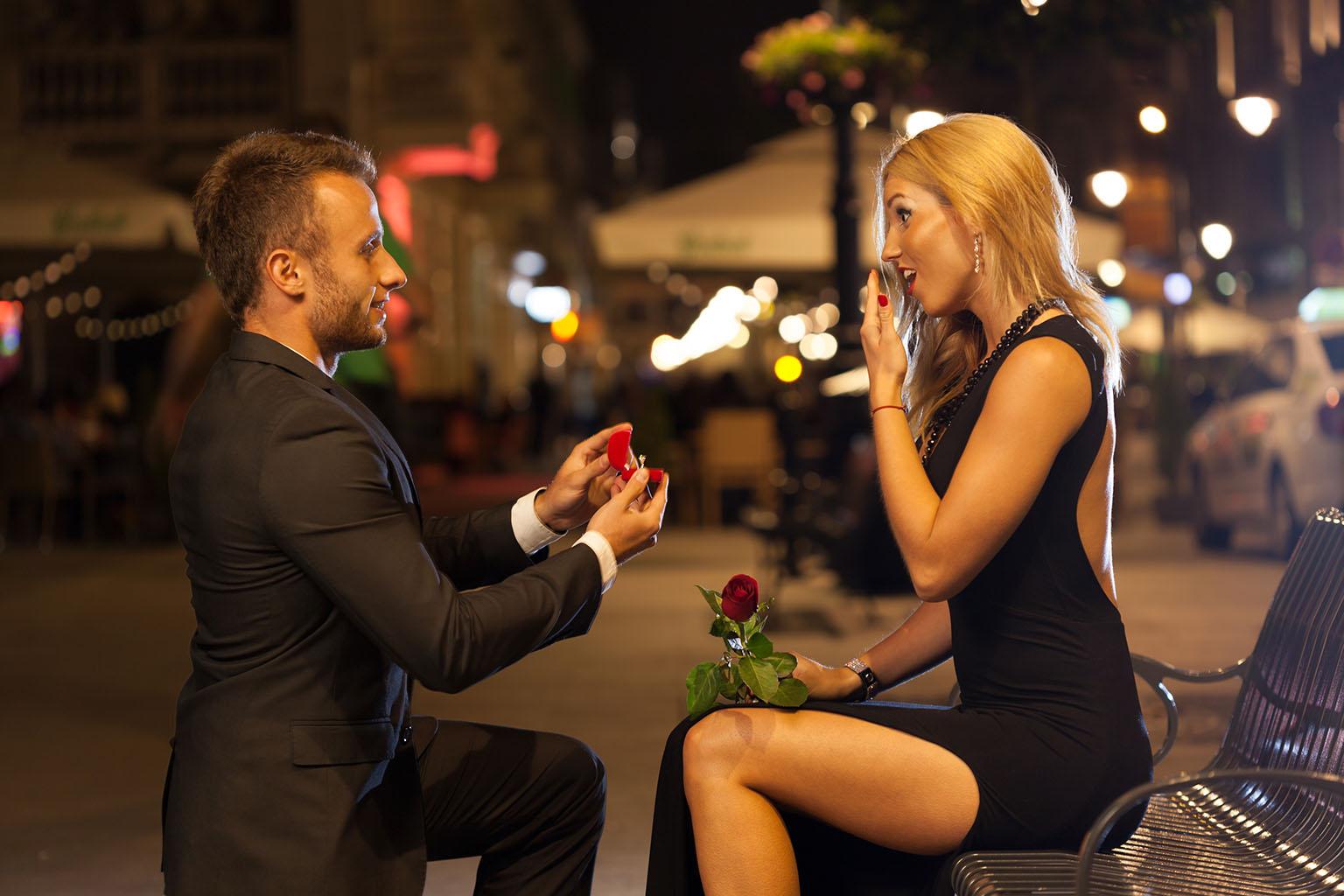 Hombre le propone matrimonio a su pareja en un banco de la ciudad y ella se sorprende poniéndose la mano en la boca, mientras su pareja saca su anillo en una de las pedidas de matrimonio más románticas.